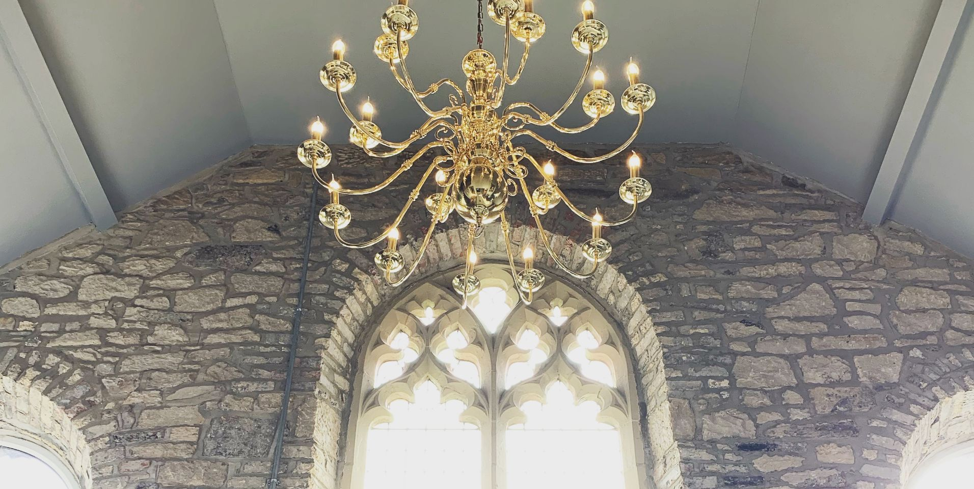 Traditional Flemish style chandelier in polished brass .